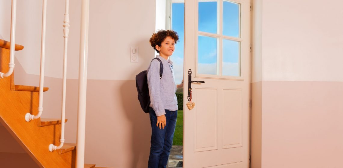 Full-length portrait of preteen curly boy standing at hallway, getting ready to go out or coming back home from school